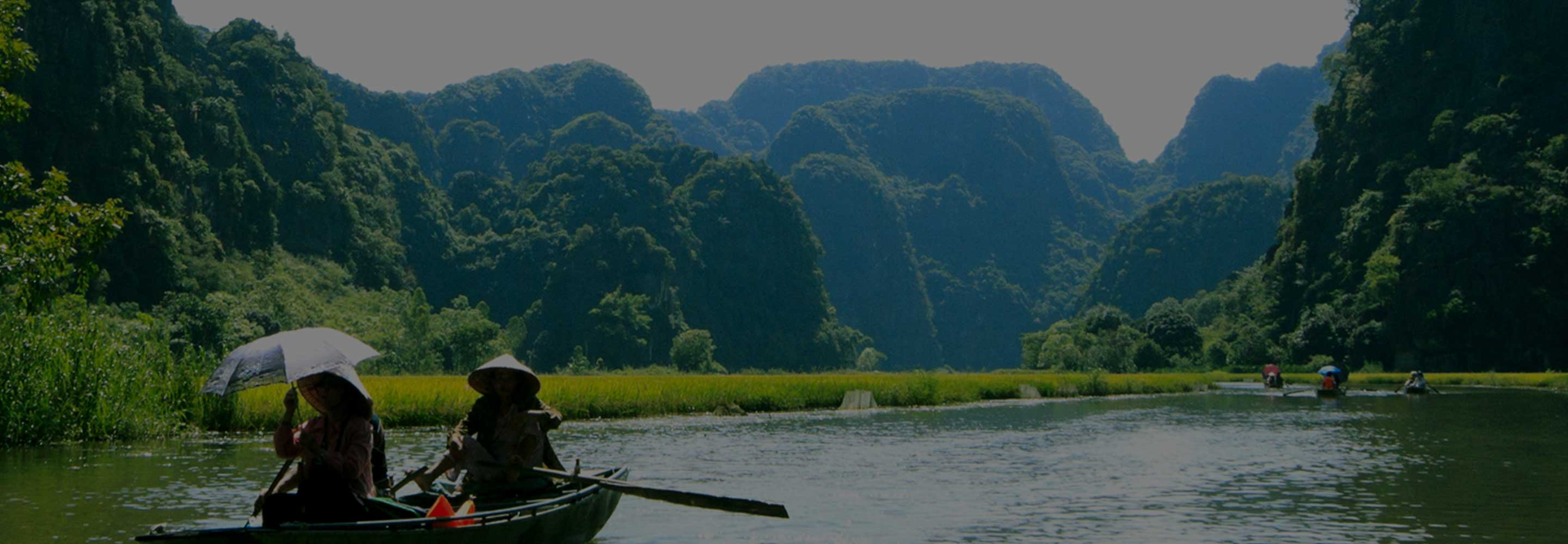 People in rowboats on river with lush green mountains in background