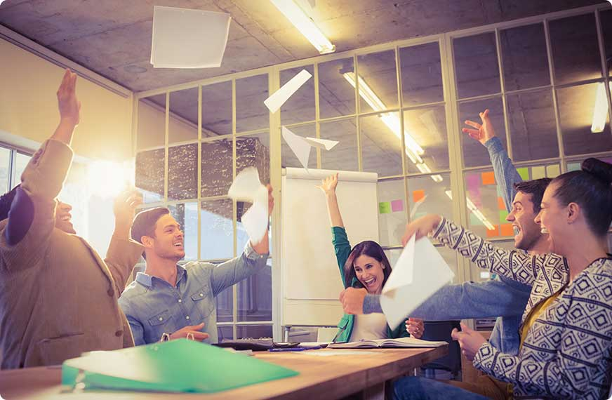 Office workers throwing papers in the air in meeting room
