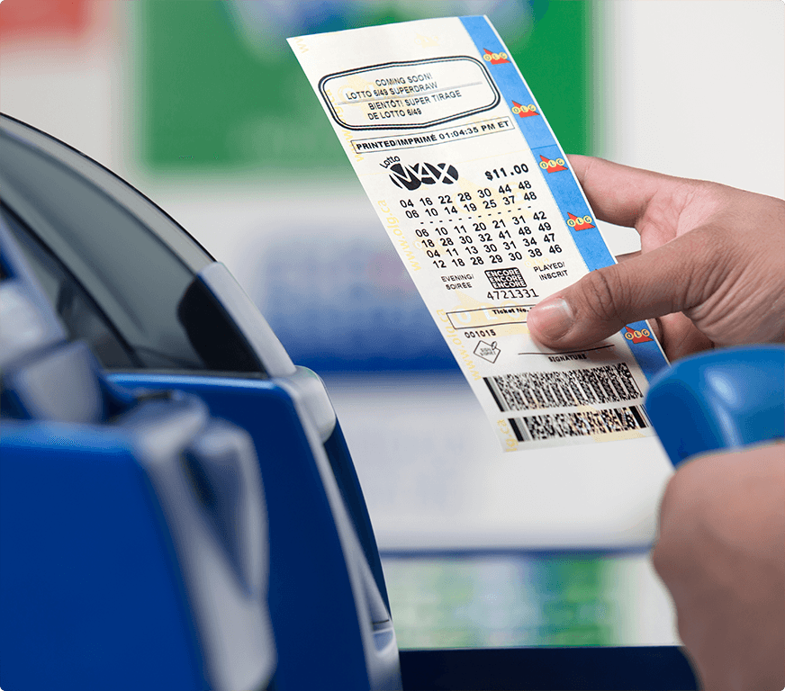 Main qui tient un billet de LOTTO MAX