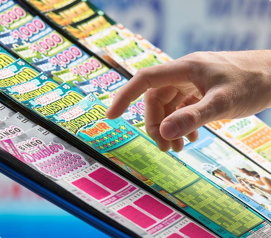 Hand choosing a scratch card at OLG retailer