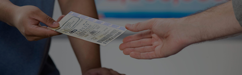Gros plan de la main d'une personne qui remet un billet de loterie à une autre personne