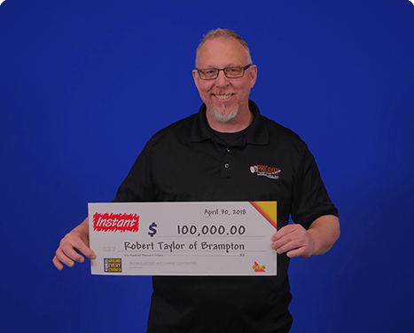 man holding 100,000 dollar cheque from winning instant 2018