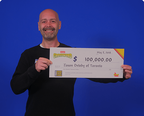 man holding 100,000 dollar cheque from winning instant crossword 2018