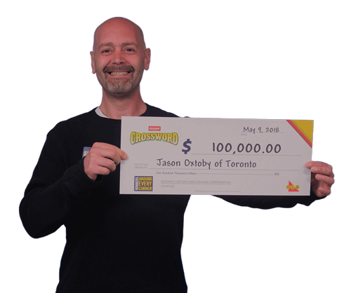 man holding 100,000 dollar cheque from instant crossword 2018