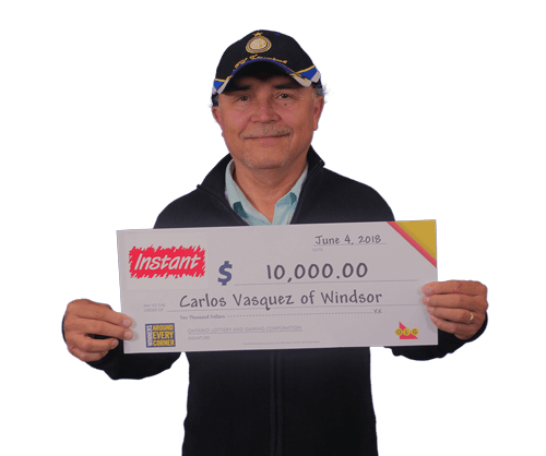 man holding 10,000 dollar cheque from winning instant