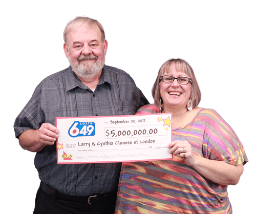 couple holding 5 million dollar cheque from lotto 649