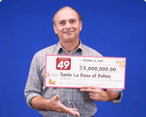 man holding 2 million dollar cheque from ontario 49