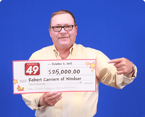 man holding 25,000 dollar cheque from ontario 49