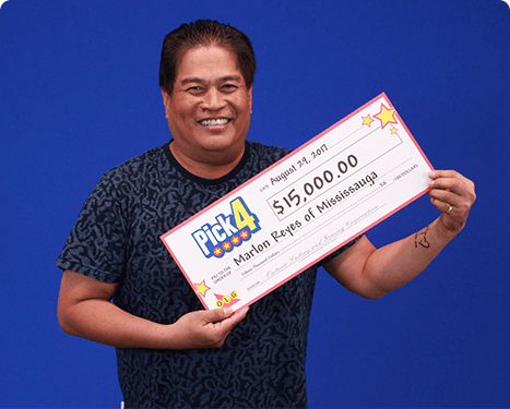 man holding 15,000 cheque from pick four