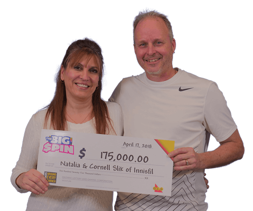 couple holding 175,000 dollar cheque from the big spin